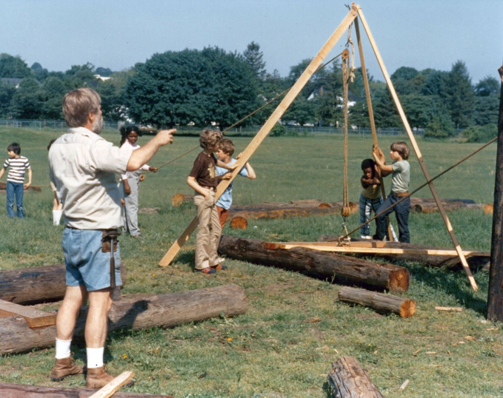 Allan Anderson helps students raise a log structure